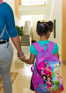 Photo of a child and mother walking down a hallway