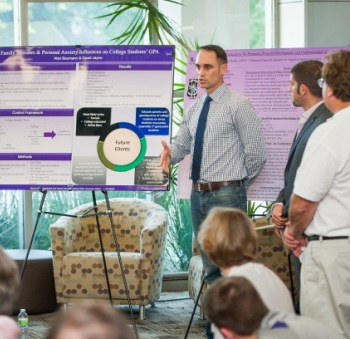 David Jayne presents research he and Allan Baumann did as part of their Ph.D. studies at a research forum in Justin Hall this summer.